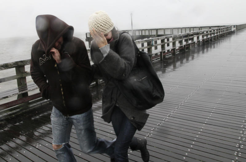 People brave high winds and blowing sand as they walk on Steeplechase Pier at Coney Island in the Brooklyn borough of New York as Hurricane Sandy arrives, Monday, Oct. 29, 2012. Hurricane Sandy continued on its path Monday, as the storm forced the shutdown of mass transit, schools and financial markets, sending coastal residents fleeing, and threatening a dangerous mix of high winds and soaking rain. (AP Photo/Mark Lennihan)