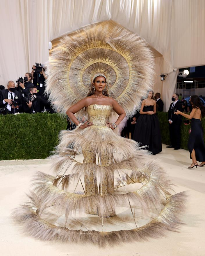 Iman wears a tiered dress and matching headpiece at the Met Gala.