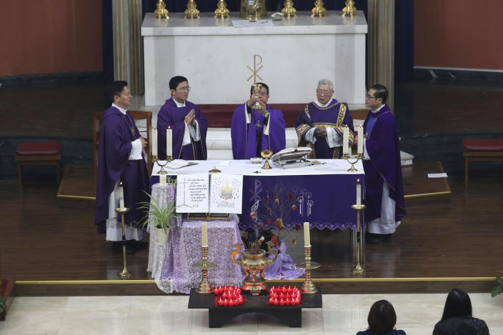 Father Simon Thang Duc Nguyen, center, leads the congregation during a Mass and vigil for the 39 victims found dead inside the back of a truck in Grays, Essex, at The Holy Name and Our Lady of the Sacred Heart Church, east London's Vietnamese church on Saturday, Nov. 2, 2019. All those killed were Vietnamese nationals, British police said. (Yui Mok/PA via AP)