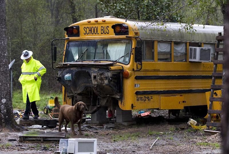 FILE - In a Wednesday, March 7, 2012 file photo, a Montgomery Count sheriff's deputy walks away from an old school bus where two children were found living on their own, in Spendora, Texas. On Tuesday, Jan. 22., 2013, a judge in Conroe, Texas dismissed the custody case against Mark and Sherrie Shorten, who were in prison when the children, then 11 and 5, were found living alone. The Shortens had left the children in the care of an aunt but she became overwhelmed. ( AP Photo/Houston Chronicle, Brett Coomer, File) MANDATORY CREDIT
