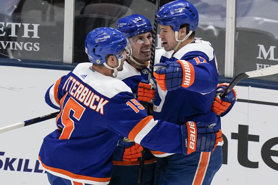 New York Islanders' Matt Martin, right, celebrates with teammates Casey Cizikas, center, and Cal Clutterbuck after scoring a goal during the third period of an NHL hockey game against the Buffalo Sabres Thursday, March 4, 2021, in Uniondale, N.Y. The Islanders won 5-2. (AP Photo/Frank Franklin II)