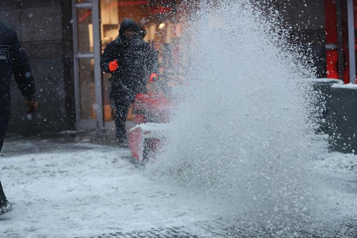 <p>A worker with a snowblower clears sidewalks in Times Square in New York, Thursday morning, Jan. 4, 2018. A massive winter storm swept from the Carolinas to Maine on Thursday, dumping snow along the coast and bringing strong winds that will usher in possible record-breaking cold. (Photo: Gordon Donovan/Yahoo News) </p>