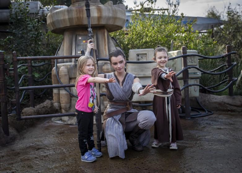 ANAHEIM, CALIF. -- THURSDAY, JANUARY 16, 2020: A cast member dressed as Rey poses for a photo with Penny Remaklus, 4, left, and Adelaide Remaklus, 7, of Ferndale, Washington, during media preview of Star Wars: Rise of the Resistance Media Preview at the Disneyland Resort in Anaheim, Calif., on Jan. 16, 2020. Star Wars: Galaxy's Edge (Allen J. Schaben / Los Angeles Times)