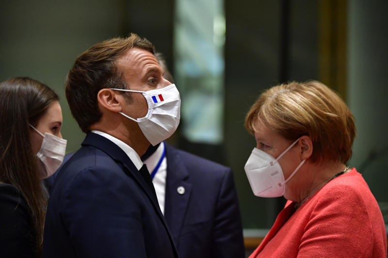 From left, Finland's Prime Minister Sanna Marin, French President Emmanuel Macron and German Chancellor Angela Merkel attend a round table meeting at an EU summit in Brussels, Monday, July 20, 2020. Weary European Union leaders are expressing cautious optimism that a deal is in sight on their fourth day of wrangling over an unprecedented budget and coronavirus recovery fund. (John Thys, Pool Photo via AP)