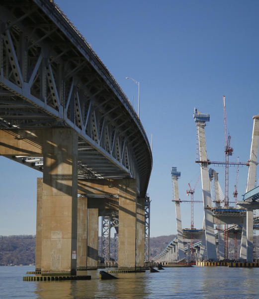 FILE - This Tuesday, Dec. 20, 2016 file photo shows the old Tappan Zee Bridge, left, during construction of its replacement, the Gov. Mario M. Cuomo Bridge, right, in Tarrytown, N.Y. Panels from the old bridge will soon be carrying a few dozen cars, pickup trucks and farm tractors over meandering streams after several counties requested salvaging some of the about 150 50-foot-long deck panels. (AP Photo/Seth Wenig, File)