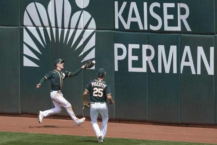 Oakland Athletics center fielder Mark Canha, left, cannot catch a two-run double hit by Houston Astros' Yuli Gurriel during the third inning of a baseball game in Oakland, Calif., Sunday, April 4, 2021. Also pictured is Athletics right fielder Stephen Piscotty (25). (AP Photo/Jeff Chiu)