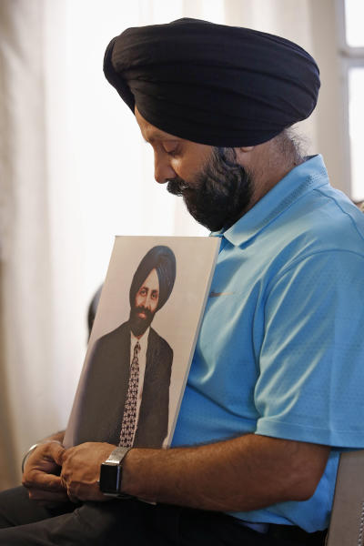 FILE - In this Aug. 19, 2016, file photo, Indian Sikh immigrant Rana Singh Sodhi holds a photograph of his brother Balbir Singh Sodhi, who was gunned down at a gas station in Mesa, Ariz., in a hate crime four days after the Sept. 11, 2001 terrorist attacks. Sodhi has preached a message of peace and tolerance in hopes of helping others better understand his religion, the fifth largest in the world with some 25 million adherents including a half-million in the United States. Sikh men typically wear turbans and beards, which makes some people mistake them as Muslims. (AP Photo/Ross D. Franklin, File)