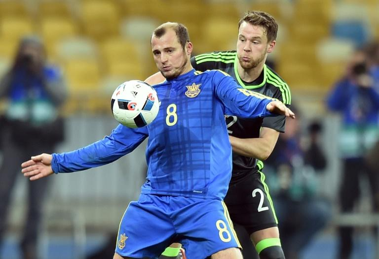 Ukraine's Roman Zozulya  (L) vies with Wales' Chris Gunter  during the international friendly football match between Ukraine and Wales at the Olimpiyskiy stadium in Kiev on March 28, 2016