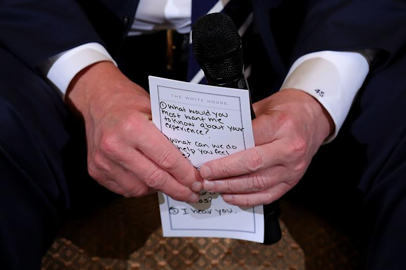 President Donald Trump holds his notes while hosting a listening session with student survivors of mass shootings.
