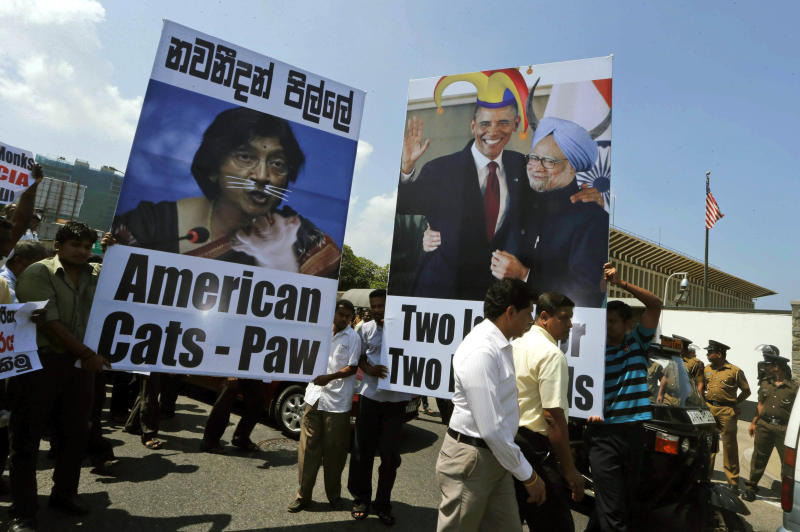 Sri Lankan government supporters carry placards during a protest outside the U.S. Embassy against a United States-sponsored draft resolution discussed at the United Nations Human Rights Council in Geneva, Thursday, March 21, 2013, in Colombo, Sri Lanka,. The resolution, if carried out, is expected to urge Sri Lanka to investigate allegations of serious human rights violations in the country's civil war. The protesters call it an interference in the country's domestic affairs. The placard at left shows a portrait of U.N. Human Rights chief Navi Pillay with her name written in Sinhalese. (AP Photo/Eranga Jayawardena)