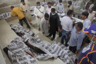 People identify the bodies of their relatives, who were died in a factory fire, at a morgue of a hospital, in Karachi, Pakistan, Friday, Aug. 27, 2021. A massive fire broke out at a chemical factory in Pakistan's southern port city of Karachi on Friday, killing some workers and injuring several others, police and a government spokesman said. (AP Photo/Ikram Suri)