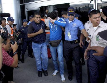 Policemen escort one of five Syrian men detained at Toncontin international airport in Tegucigalpa, Honduras, November 18, 2015. Honduran authorities have detained five Syrian nationals who were trying to reach the United States using stolen Greek passports, but there are no signs of any links to last week's attacks in Paris, police said. The Syrian men were held late on Tuesday in the Honduran capital, Tegucigalpa, on arrival from Costa Rica, and had been planning to head to the border with neighboring Guatemala. The passports had been doctored to replace the photographs with those of the Syrians, police said. REUTERS/Stringer EDITORIAL USE ONLY. NO RESALES. NO ARCHIVE.