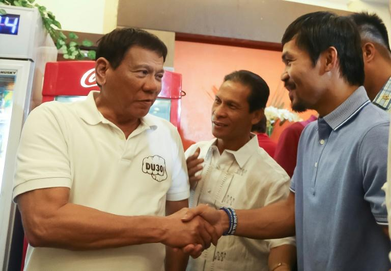 Manny Pacquiao, elected to the Senate earlier this year, is seen with Philippines' President Rodrigo Duterte, left
