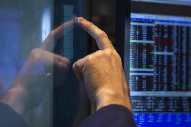 A trader reaches up to adjust his screen as he works on the floor of the New York Stock Exchange
