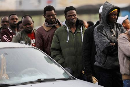 African migrants wait in line for the opening of the Population and Immigration Authority office in Bnei Brak