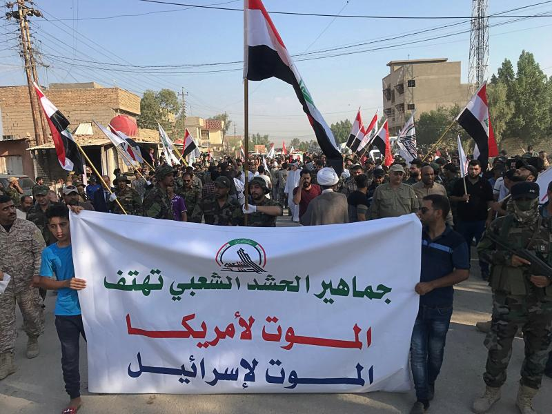 """Mourners hold a banner with Arabic that reads, """"Masses of the Popular Mobilization Forces chant death to America, death to Israel"""" during the funeral procession of Abu Ali al-Dabi, a fighter of the Popular Mobilization Forces, who was killed in a drone attack, in Baghdad, Iraq, Monday, Aug. 26, 2019. Two unidentified drones killed two Iraqi members of the Iran-backed paramilitary force on Sunday, the group said in a statement, saying the attack took place in Iraq near the border with Syria. (AP Photo/Ali Abdul Hassan)"""