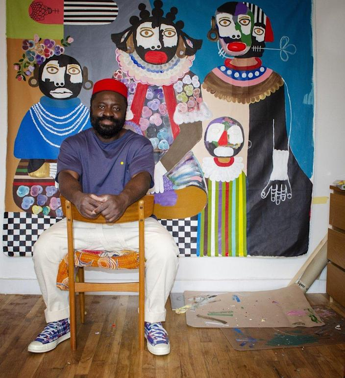 Kojo Marfo poses in his studio in front of one of his paintings