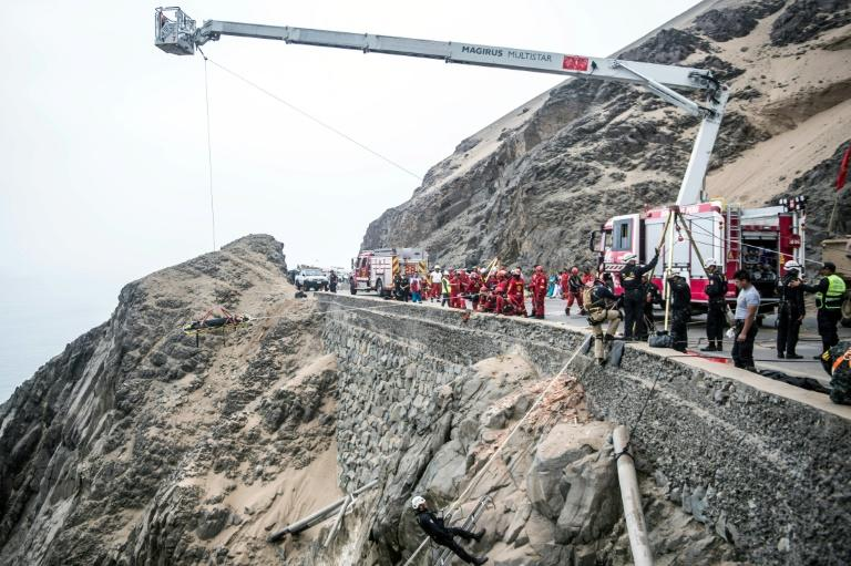 Rescuers, police and firefighters work at the scene after a bus plunged over a cliff when it collided with a truck on a coastal highway in Peru; the death toll now stands at 50