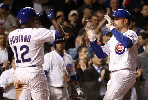 Chicago Cubs' Alfonso Soriano (12) greets Nate Schierholtz at home after the pair scored on Schierholtz's two-run home run off St. Louis Cardinals starting pitcher Lance Lynn during the fourth inning of a baseball game, Tuesday, May 7, 2013, in Chicago. (AP Photo/Charles Rex Arbogast)