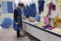 In this image from video, Kiyoko Mori, 65, the head of indigo dye group called Japan Blue, looks at displayed indigo dyed artwork at a community center where residents evacuated when the massive earthquake hit the area in 2011, in Minamisoma, Fukushima Prefecture, northeastern Japan, on Feb. 20, 2021. After the Fukushima nuclear plant disaster a decade ago, nearby farmers weren't allowed to grow crops for two years because of radiation. After the restriction was lifted, two farmers in the town of Minamisoma found an unusual way to rebuild their lives and help their destroyed community. Mori and Yoshiko Ogura planted indigo and soon began dying fabric with dye produced from the plants. (AP Photo/Chisato Tanaka)