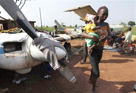 A woman walks while holding a baby at a camp in Bangui December 12, 2013.REUTERS/Emmanuel Braun