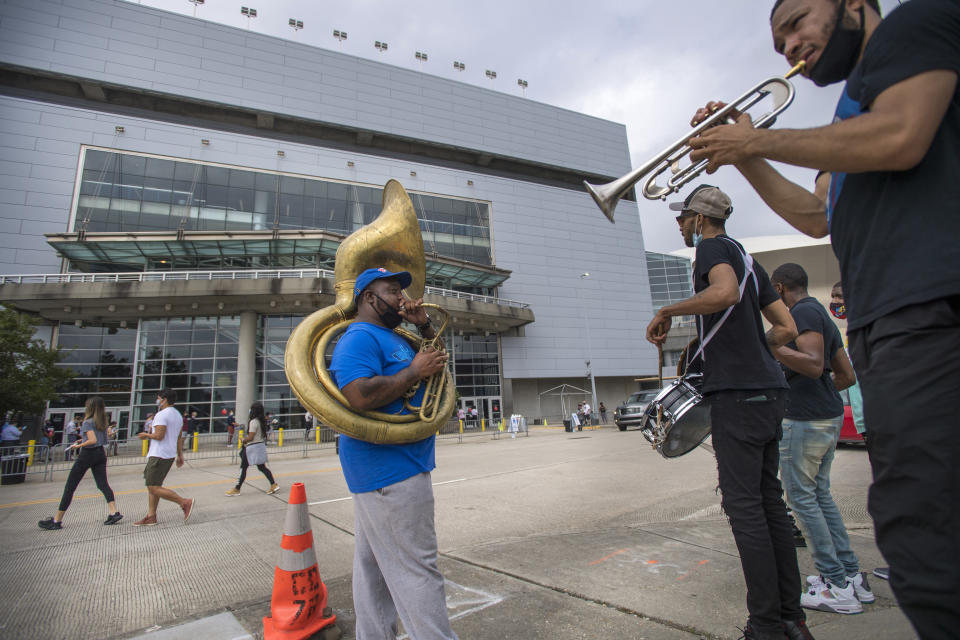 Members of the Rebirth Brass Band, from left, tuba player Clifton Smith, drummer Jenard Andrews, bass drummer Thaddeus Ramsey, and trumpet player Glenn Hall, stand across the street from the Smoothie King Center playing songs for the long line of early voters standing outside the sport complex in New Orleans, Tuesday, Oct. 27, 2020. (Chris Granger/The Advocate via AP)