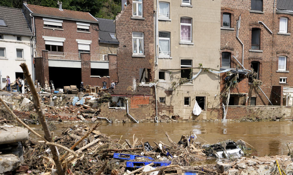 FILE-In this July 17, 2021 file photo a car sits upside down in the River and houses are damaged after flooding in Pepinster, Belgium. Scientists say global warming makes the kind of extreme rainfall that caused deadly flash floods in western Europe last month more likely, though it remains unclear exactly how much. (AP Photo/Virginia Mayo)