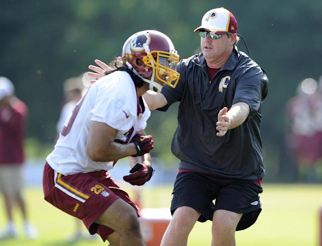 Washington Redskins head coach Jay Gruden takes part in a drill with running back Roy Helu, Jr., left, during an NFL football minicamp, Tuesday, June 17, 2014, in Ashburn, Va. (AP Photo/Nick Wass)