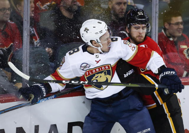 Florida Panthers' Jayce Hawryluk, left, is checked by Calgary Flames' Noah Hanifin during second-period NHL hockey game action in Calgary, Alberta, Friday, Jan. 11, 2019. (Jeff McIntosh/The Canadian Press via AP)