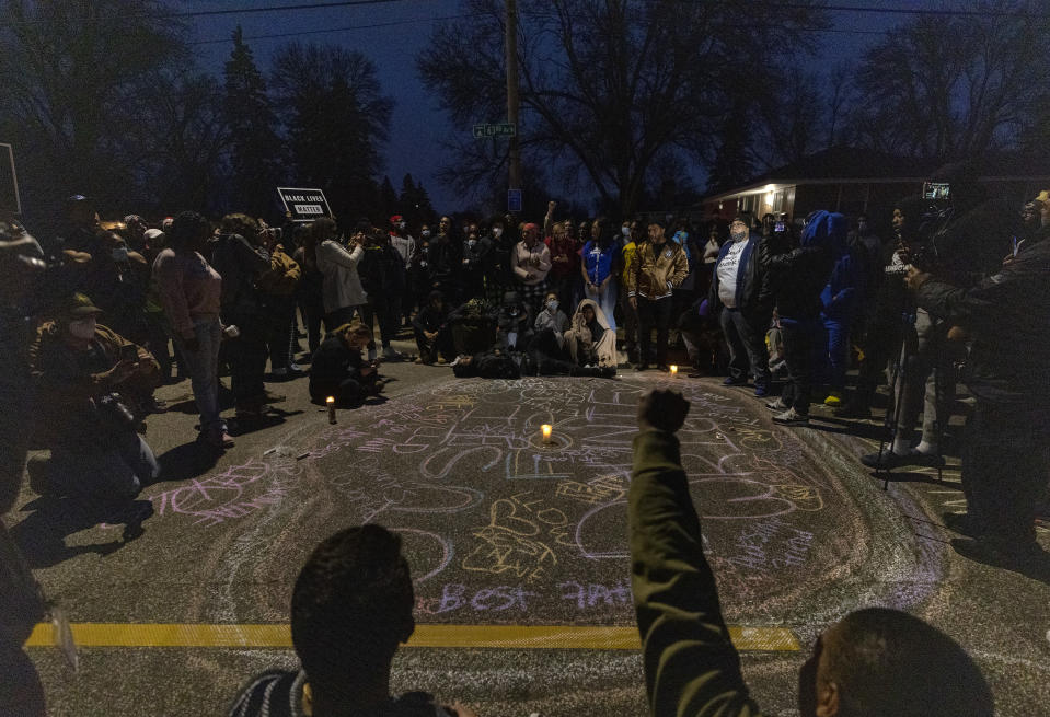 A crowd forms a circle around a memorial for Daunte Wright, in Brooklyn Center, Minn., Sunday, April 11, 2021. Wright's family told a crowd that he was shot by police Sunday before getting back into his car and driving away, then crashing the vehicle several blocks away. The family said Wright was later pronounced dead. (Carlos Gonzalez/Star Tribune via AP)