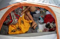 An asylum-seeking migrant youth, who was apprehended and returned to Mexico under Title 42 after crossing the border from Mexico into the U.S., rests in a public square where hundreds of migrants live in tents, in Reynosa