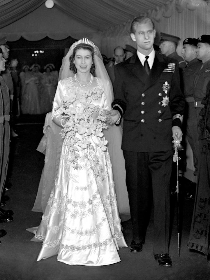 <p>The Queen, then Princess Elizabeth, married Philip Mountbatten, Duke of Edinburgh at Westminster Abbey on 20 November 1947. For the occasion, Elizabeth wore an ivory silk satin dress by royal coutierer Norman Hartnell. It featured elaborate embroidered star lily and orange blossom motifs and was encrusted with 10,000 seed pearls imported from America.<em> [Photo: PA] </em> </p>