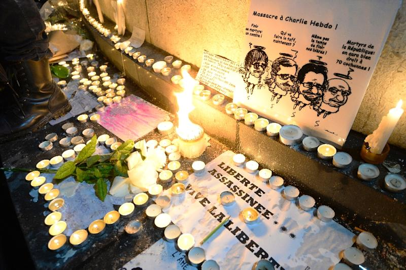 Candles are lit around a drawing depicting late French cartoonists Cabu, Charb, Tignous and Wolinski during a rally at Republic Square in Paris on January 8, 2015, a day after a deadly attack on the headquarters of satirical magazine Charlie Hebdo