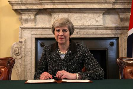 FILE PHOTO: British Prime Minister Theresa May in the cabinet office signs the official letter to European Council President Donald Tusk invoking Article 50