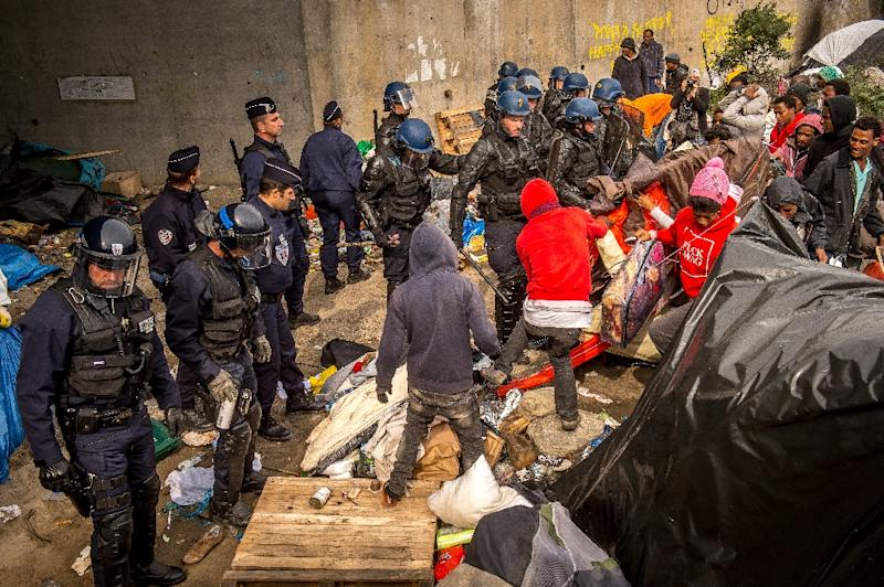 French police officers proceed with operations during the eviction of around 200 Syrian refugees from a camp site in Calais, northern France, on September 21, 2015