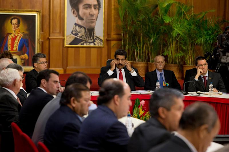 Venezuela's President Nicolas Maduro, top center, looks toward leaders of the opposition at the start of a meeting at Miraflores presidential palace in Caracas, Venezuela, Thursday, April 10, 2014. The Vatican is sponsoring the first talks aimed at reconciliation since protests began in early February. Maduro's opponents blame his government for destroying the oil-rich economy and stamping out dissent, while Maduro claims he's the target of U.S.-backed coup attempt. (AP Photo/Fernando Llano)