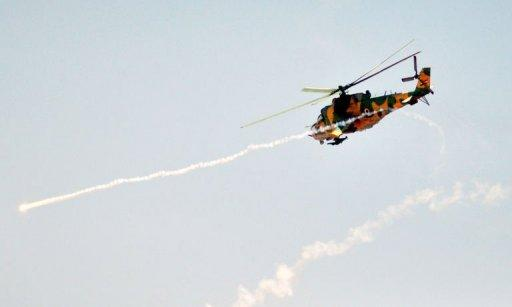 A handout picture released by the official Syrian Arab News Agency (SANA) shows a Syrian military attack helicopter firing missiles during Syrian army maneuvers at an undisclosed location in Syria