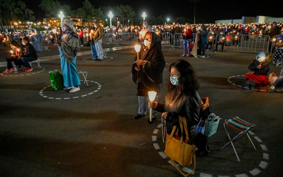 Faithful hold lit candles during the evening procession of candles at the sanctuary on the first day of the ceremonies - Corbis News