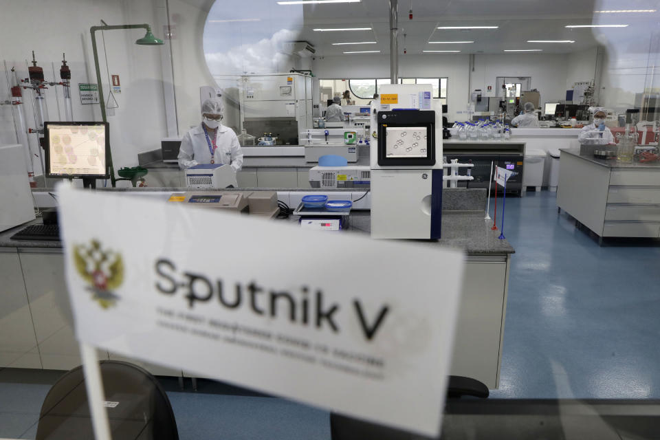 Laboratory workers work in the pilot production phase of Russia's Sputnik V Coronavirus vaccine for COVID-19 at the pharmaceutical company Uniao Quimica in Brasilia, Brazil, Monday, Jan. 25, 2021. (AP Photo/Eraldo Peres)