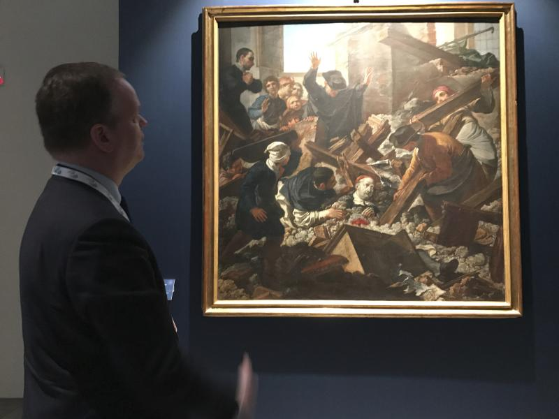 In this photo taken on Friday, March 31, 2017, Uffizi Gallery director Eike Schmidt looks at the painting ''The Miracle of San Filippo,'' depicting the future pope Benedict XIII surviving an earthquake in 1688, at the Uffizi Gallery, in Florence, Italy. The Uffizi Gallery is showing solidarity with the art-rich, quake-stricken Marche region with an exhibit of treasures saved from a series of earthquakes last year. Eike Schmidt said during a walk-through Friday after the first meeting of culture ministers form the Group of Seven industrialized nations that the 29 selected works were from churches, museums and other buildings either damaged or destroyed in powerful quakes last August and October. (AP Photo/Colleen Barry)