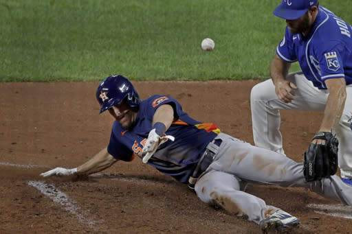 Houston Astros' Myles, left, Straw beats the tag at home by Kansas City Royals relief pitcher Greg Holland to score on a wild pitch during the seventh inning of an exhibition baseball game in Kansas City, Mo., Monday, July 20, 2020. (AP Photo/Charlie Riedel)