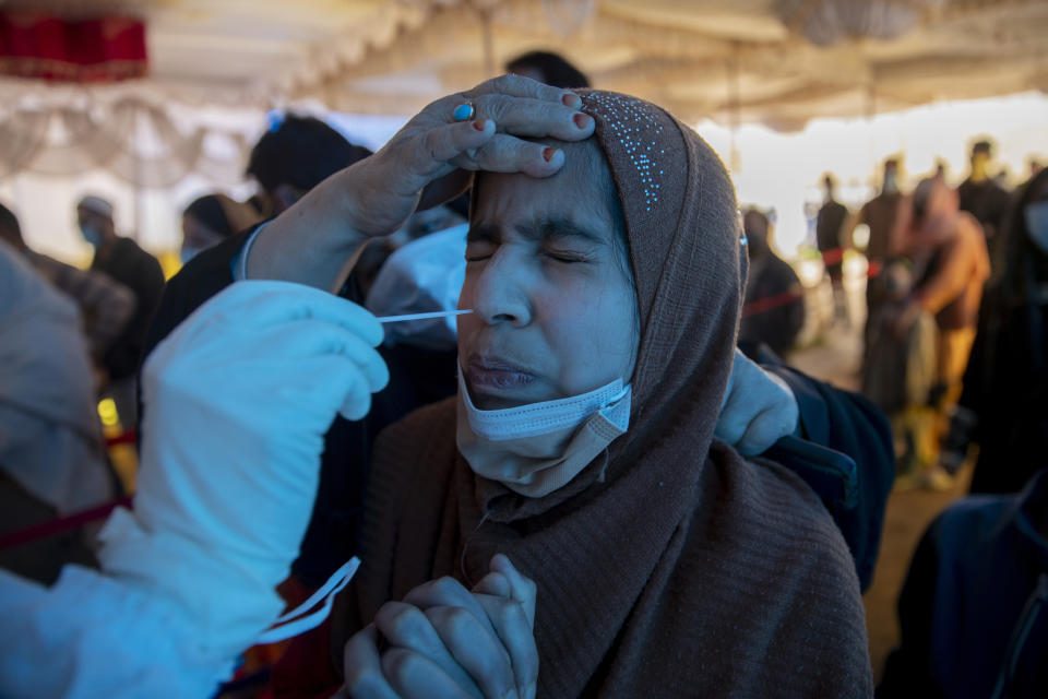 A health worker takes a nasal swab sample of a Kashmiri girl to test for COVID-19 in Srinagar, Indian-controlled Kashmir on April 21, 2021. (Dar Yasin/AP)