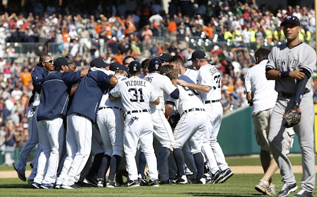 New York Yankees shortstop Derek Jeter, right, walks off the field as Detroit Tigers' Alex Avila celebrates with teammates after hitting a walk off single to score Bryan Holladay against the New York Yankees in the ninth inning of a baseball game in Detroit Thursday, Aug. 28, 2014. Detroit won 3-2. (AP Photo/Paul Sancya)