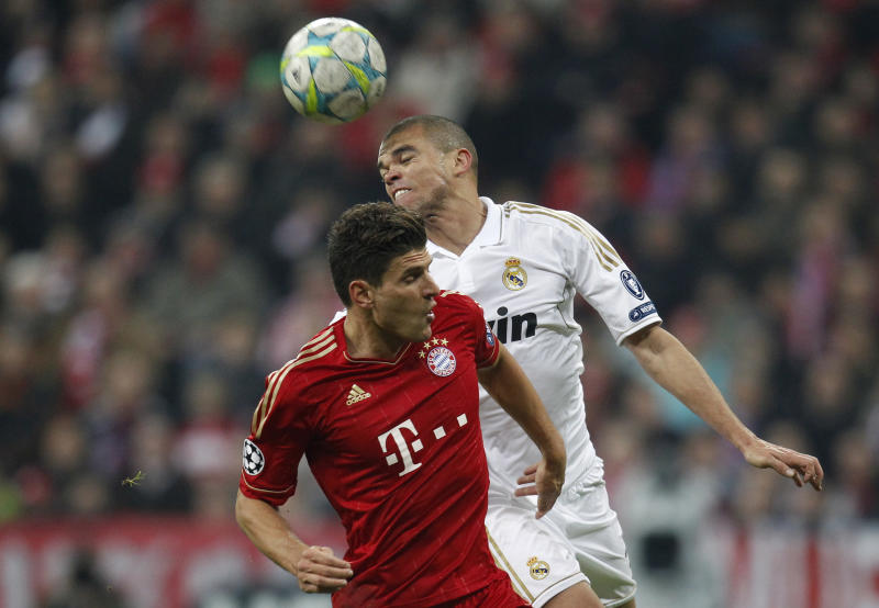 Madrid's Pepe, right and Bayern's Mario Gomez go for a header during the Champions League first leg semifinal soccer match between Bayern Munich and Real Madrid in Munich, southern Germany, Tuesday, April 17, 2012. (AP Photo/Matthias Schrader)