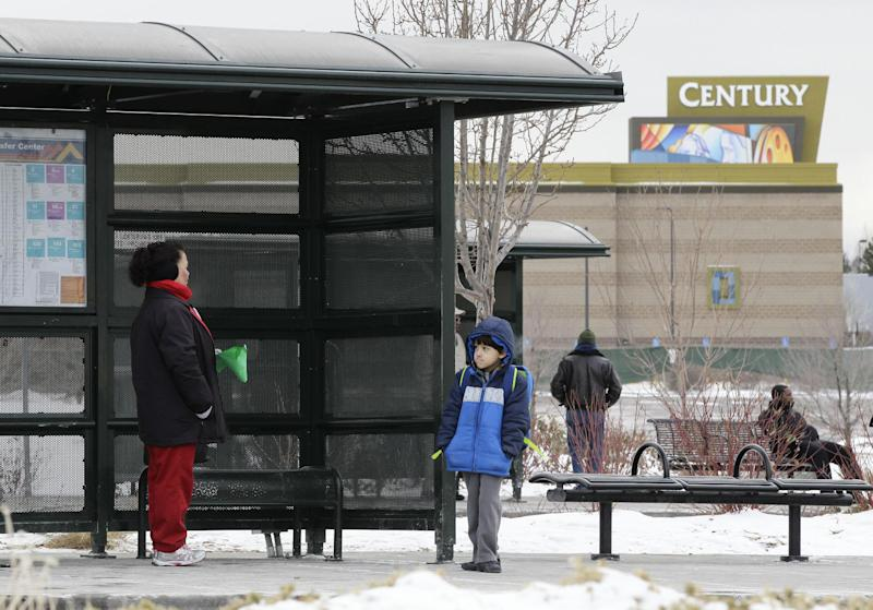 A woman and her grandson wait for a bus, near the fenced-in Century movie theater, the site of the deadly 2011 shootings, in Aurora, Colorado, Tuesday, Jan. 15, 2013. Victims and their families are being permitted to tour the Colorado movie theater where 12 people were killed and dozens were injured. The family visits, which began on Tuesday and will continue Wednesday, are to be followed by the Theater's reopening to the public on Friday. (AP Photo/Brennan Linsley)