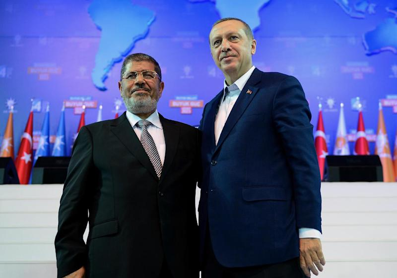 FILE -- In this Sunday, Sept. 30, 2012 file photo provided by Turkish Prime Minister's Press Service,Turkey's Prime Minister Recep Tayyip Erdogan, right, and Egyptian President Mohammed Morsi salute the members of Turkey's ruling Justice and Development Party in Ankara, Turkey. Egyptians are closely following protests in Turkey, a country that has provided the heavily polarized and increasingly impoverished Egyptians with a tantalizing model for marrying Islamist government with a secular establishment and achieving prosperity along the way. For the first time in a decade of power, Erdogan appeared vulnerable and embattled in front of tens of thousands of protesters converging every day at dozens of cities across Turkey for more than a week. (AP Photo/Kayhan Ozer, File)