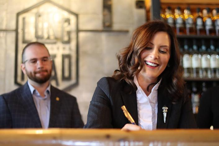 Michigan Sen. Jeremy Moss, D-Southfield, stands behind Gov. Gretchen Whitmer during a bill signing at Long Road Distillers in Grand Rapids.
