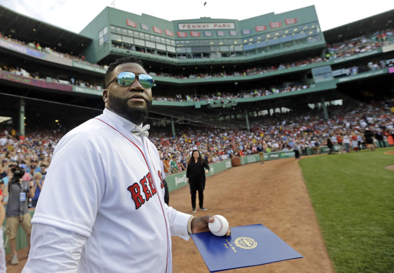 Retired Boston Red Sox player David Ortiz looks at the large television screen Friday, June 23, 2017, at Fenway Park in Boston as the team retired his jersey No. 34 worn when he led the franchise to three World Series titles. It is the 11th number retired by the Red Sox. (AP Photo/Elise Amendola)