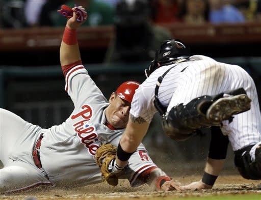 Philadelphia Phillies' Carlos Ruiz, left, slides across home plate to score a run as Houston Astros catcher Chris Snyder, right, dives to tag him during the fifth inning of a baseball game Friday, Sept. 14, 2012, in Houston. (AP Photo/David J. Phillip)