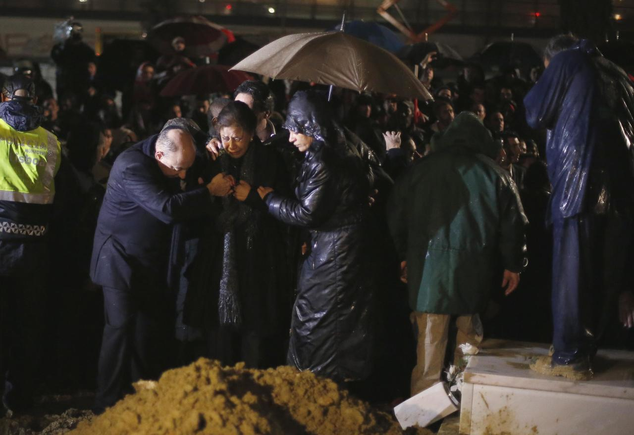 "Flora (C), wife of Eusebio, cries during the funeral of her husband at Lumiar cemetery in Lisbon January 6, 2014. Portuguese great Eusebio, top scorer at the 1966 World Cup, died on Sunday from a heart attack at the age of 71 with the small Iberian nation mourning him as an ""eternal symbol"" of their football pride. On Monday, he was honored at Luz stadium before his burial. REUTERS/Rafael Marchante (PORTUGAL - Tags: SPORT SOCCER OBITUARY)"